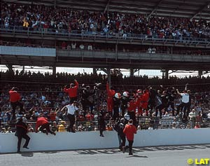 Helio Castroneves and his crew climb the fence at Indy