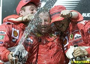 Rubens Barrichello, Jean Todt and Michael Schumacher, celebrating on the podium