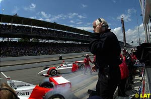 Roger Penske stands on the pit wall as his two drivers, Gil de Ferran and Helio Castroneves, exit the pits during this year's Indy 500 in which the team finished first and second